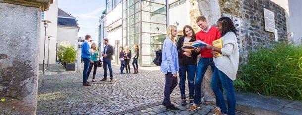 Happy students stood outside a university